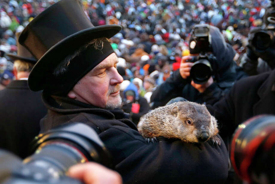 Groundhog Club Co-handler John Griffiths holds the weather predicting groundhog, Punxsutawney Phil, as he is surrounded by photographers after the club said Phil did not see his shadow and there will be an early spring on Groundhog Day, Saturday, Feb. 2, 2013 in Punxsutawney, Pa. (AP Photo/Keith Srakocic) / AP