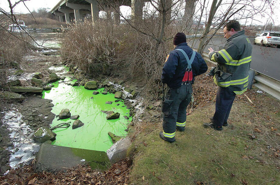 Hour photos / Alex von Kleydorff Norwalk firefighters from Engine 3 observe green fluid making its way into the Norwalk River at Selleck Street on Wednesday. / 2012 The Hour Newspapers
