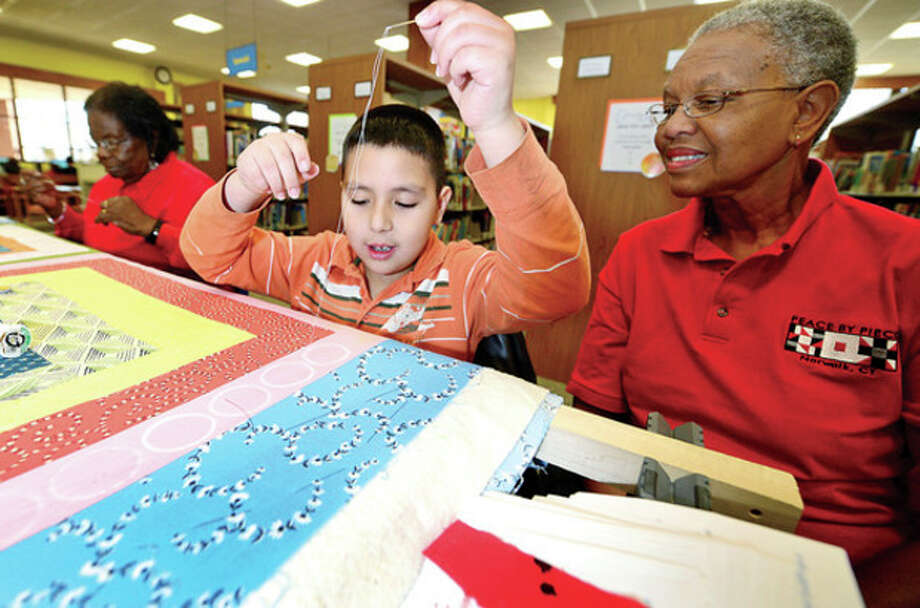"Hour photos / Erik TrautmannAbove, Eymard Navarro, 8, works with Dorothy Byrd of Peace by Piece: The Norwalk Community Quilt Project during the Norwalk Public Library's second annual ""Norwalk Has Heart Day"" combined with the ""National Take Your Child to the Library Day"" Saturday. Below, Tejal Athavia and her daughter, Ruchita, 9 months old, paint a craft project. / (C)2012, The Hour Newspapers, all rights reserved"