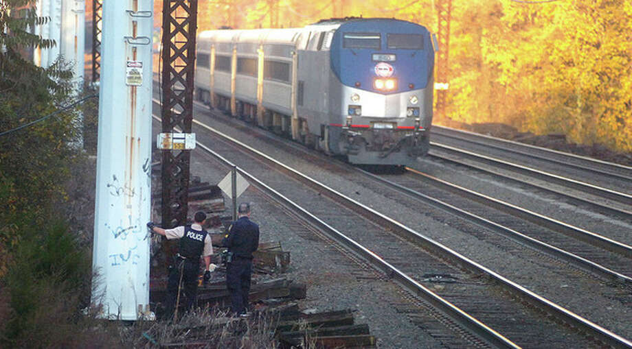 Hour Photo/ Alex von Kleydorff. MTA police and Norwalk PD look for a fugitive as they wait for a train to pass along the railroad tracks Wednesday afternoon. / 2011 The Hour Newspapers