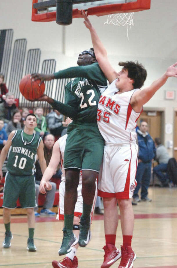 Norwalk's Roy Kane goes up for a shot as Beau Santero of New Canaan defends during Friday night's game. Norwalk held on for a 49-47 victory.Hour Photo/ Alex von Kleydorff