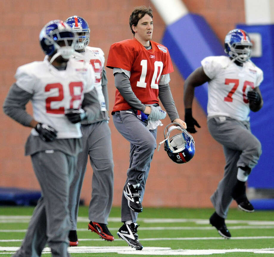 New York Giants quarterback Eli Manning loosens up during an NFL football practice Thursday, Jan. 19, 2012, in East Rutherford, N.J. The Giants travel to San Francisco to play the 49ers in the NFC championship game on Sunday, Jan. 22. (AP Photo/Bill Kostroun) / FR51951 AP