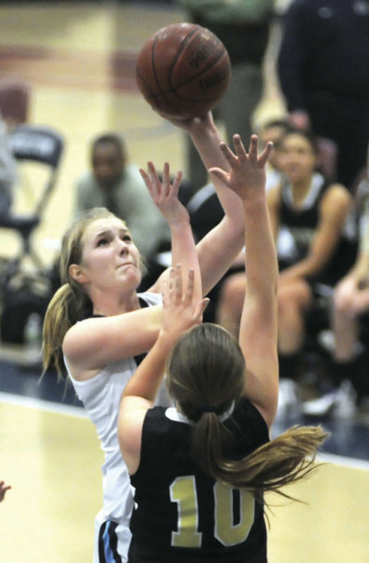 Hour photo/John Nash Wilton's Erin Cunningham, left, puts up a shot over the defense of Trumbull's Kate O'Leary during Friday night's FCIAC girls basketball game at the Zeoli Field House. Wilton won the game, 43-31.