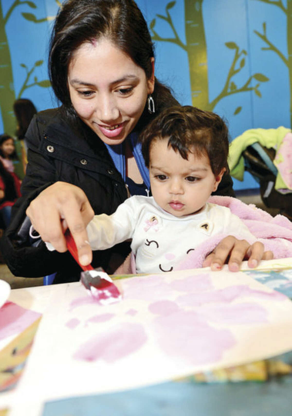 Tejal Athavia and her daughter, Ruchita, 9 months old, paint a craft project during the Norwalk Public Library 2nd annual Norwalk Has Heart Day combined with the National Take Your Child to the Library Day featuring Peace by Piece: The Norwalk Community Quilt Project Saturday. Hour photo / Erik Trautmann
