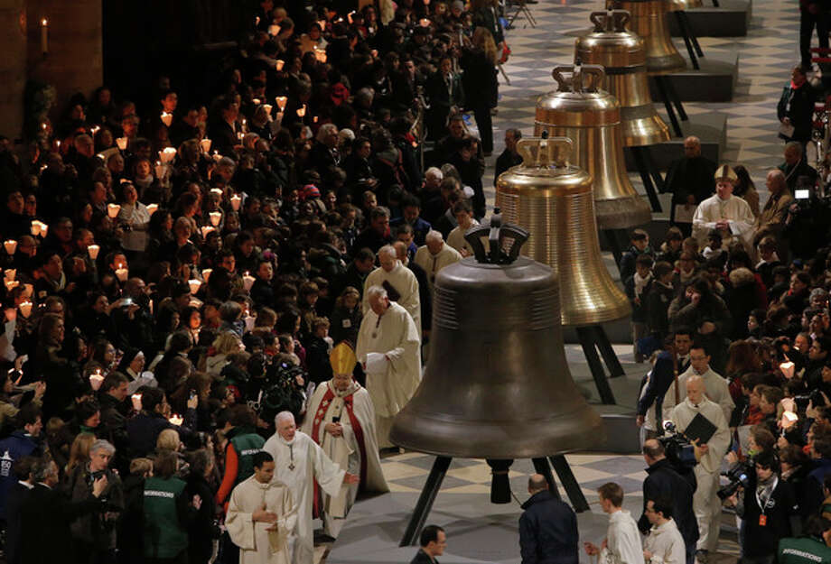 Some of the nine new bronze bells are displayed in Notre Dame cathedral during a ceremony of blessing by Paris Archbishop Andre Vingt-Trois in Paris, Saturday, Feb. 1, 2013. Nine enormous new bronze bells have made their way at Notre Dame Cathedral, helping the medieval edifice to rediscover its historical harmony. (AP Photo/Francois Mori) / AP