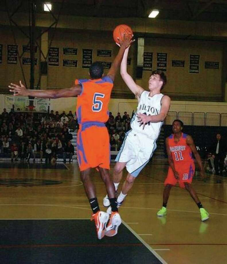 Hour photo/Alex von Kleydorff Wilton's Chris Nugent, right, is challenged by C.J. White of Danbury as he goes up for a shot during Friday night's game at Wilton's Zeoli Fieldhouse. The Warriors clinched a berth in the state tournament with a 66-60 victory. / 2012 The Hour Newspapers