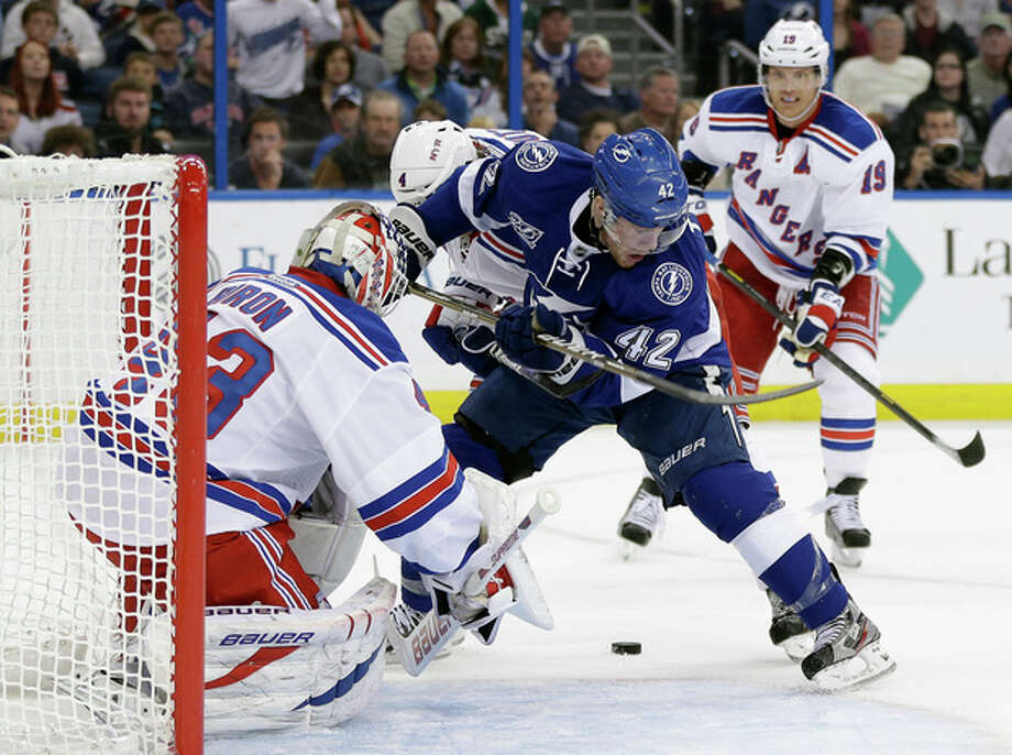 Tampa Bay Lightning center Dana Tyrell (42) loses control of the puck in front of New York Rangers goalie Martin Biron (43) during the second period of an NHL hockey game on Saturday, Feb. 2, 2013, in Tampa, Fla. Rangers' Brad Richards, right, trails the play. (AP Photo/Chris O'Meara) / AP