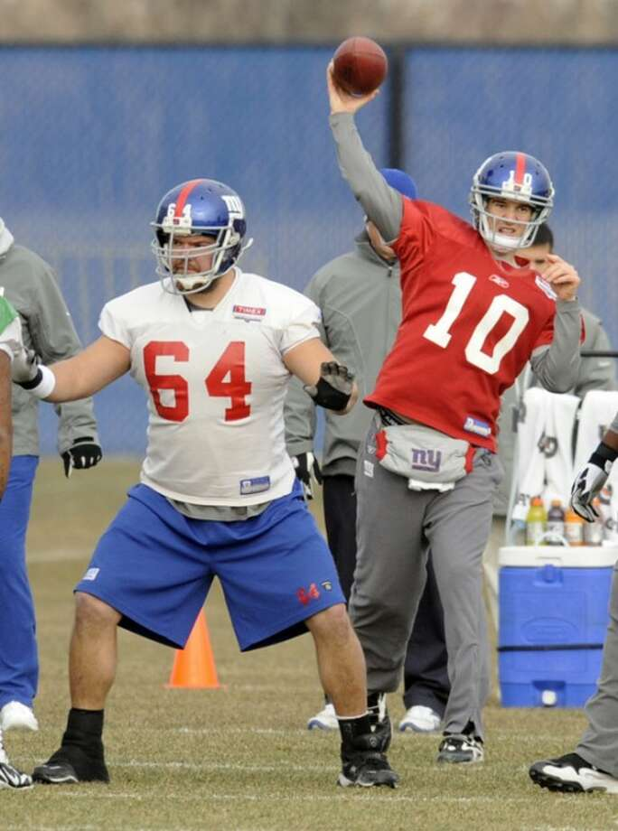 New York Giants quarterback Eli Manning (10) throws a pass as center David Baas blocks during NFL football practice Friday, Jan. 6, 2012, in East Rutherford, N.J. The Giants are slated to host the Atlanta Falcons on Sunday in a wild-card playoff game. (AP Photo/Bill Kostroun)