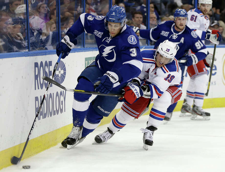 Tampa Bay Lightning defenseman Keith Aulie (3) carries the puck past New York Rangers center Brad Richards (19) during the first period of an NHL hockey game on Saturday, Feb. 2, 2013, in Tampa, Fla. (AP Photo/Chris O'Meara) / AP