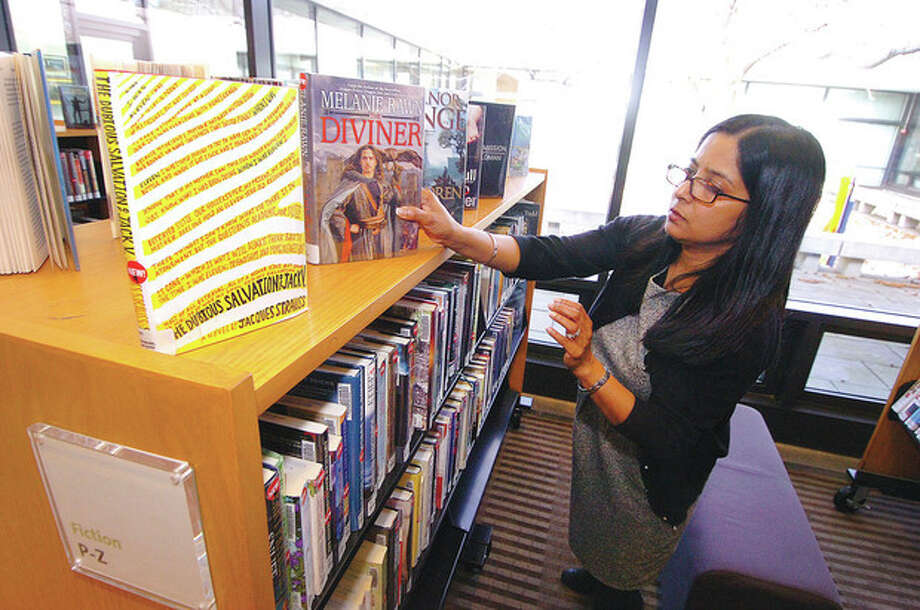 Photo by Alex von Kleydorff Seema Saksena, a circulation desk assistant at Wilton Library, places books back on the library's new arrival shelves. / 2012 The Hour Newspapers