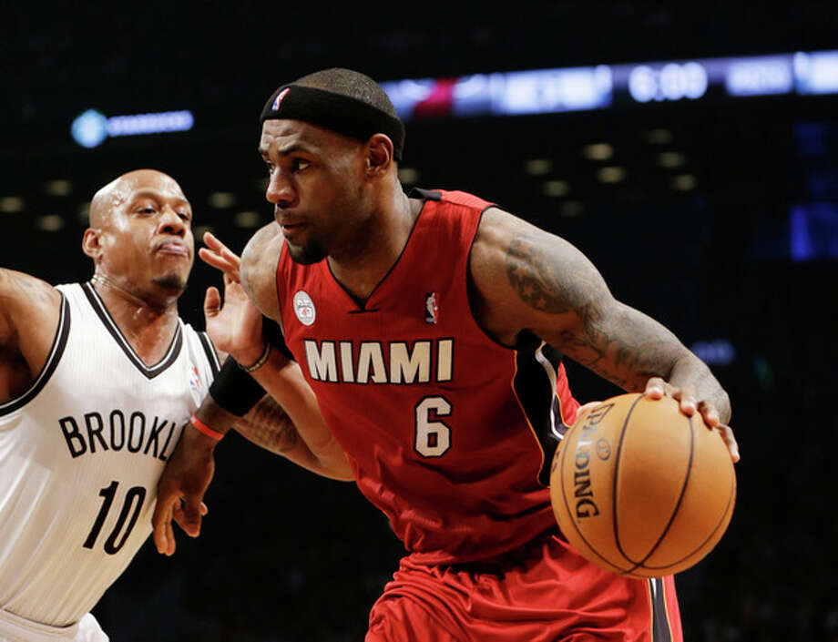 Brooklyn Nets forward Keith Bogans (10) defends as Miami Heat forward LeBron James (6) drives toward the basket in the first half of an NBA basketball game, Wednesday, Jan. 30, 2013, in New York. The Heat won 105-85. (AP Photo/Kathy Willens) / AP