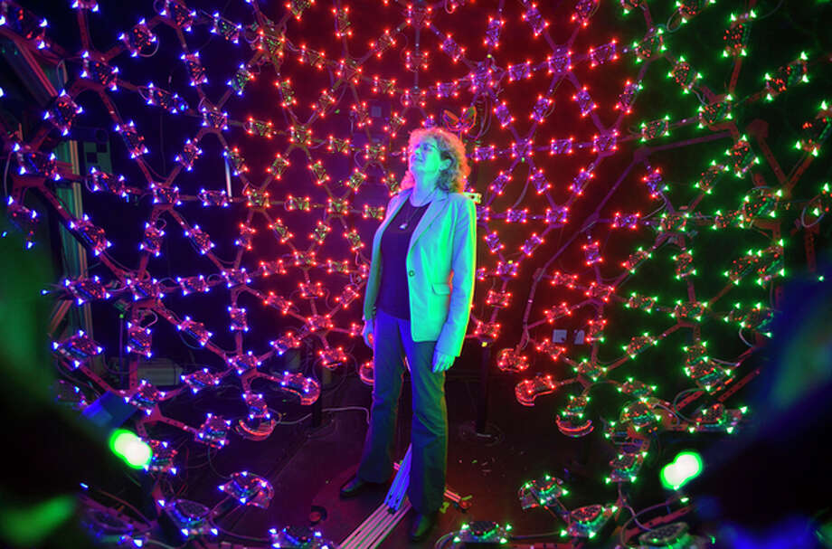 "In this photo taken Tuesday, Jan. 29, 2013, University of Southern California Institute for Creative Technologies manager, Lori Weiss relaxes to music synchronized with color LEDs, inside the Lighting Stage X, the institute's latest LED-filled sphere used to help create realistic virtual characters in Playa Vista area of Los Angeles. The technology is used by the ""Virtual Survivor Visualization,"" part of a collaboration with the Shoah Foundation to digitize aging Holocaust survivors to create three-dimensional holograms that would not only be able to tell their stories to future generations but to engage in dialogue with them. (AP Photo/Damian Dovarganes) / AP"