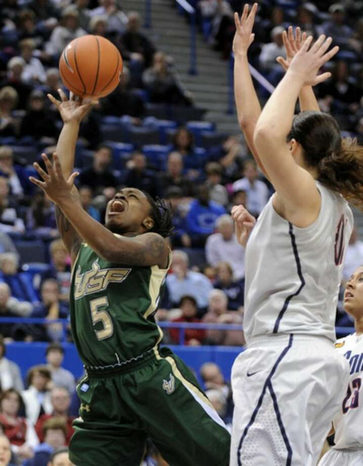 South Florida's Sasha Bernard drives past Connecticut's Stephanie Dolson during the first half of an NCAA college basketball game in Hartford, Conn., on Saturday, Jan. 28, 2012. (AP Photo/Fred Beckham)