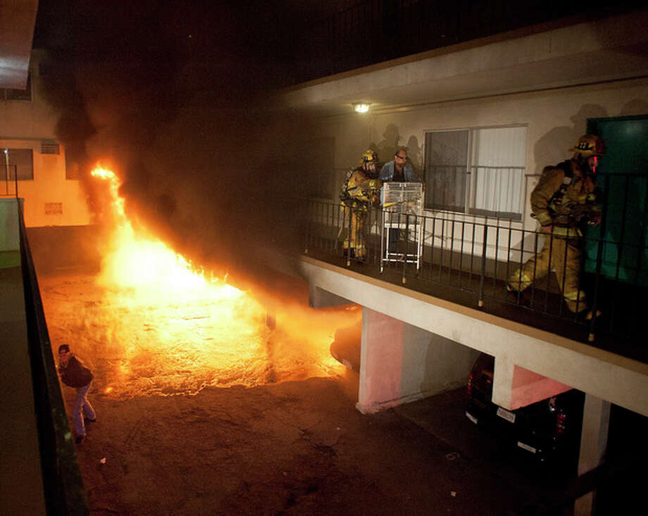 Los Angeles Fire Department firefighters assist a man out of his apartment along with a cage of birds as multiple cars burn in a carport in the Sun Valley neighborhood of Los Angeles on Saturday, Dec. 31, 2011. For the third night in a row, a rash of arson fires has sent firefighters scrambling to extinguish car fires in various neighborhoods in Los Angeles. Most of the fires on this night occurred in the San Fernando Valley. (AP Photo/Dan Steinberg) / FR158549 AP