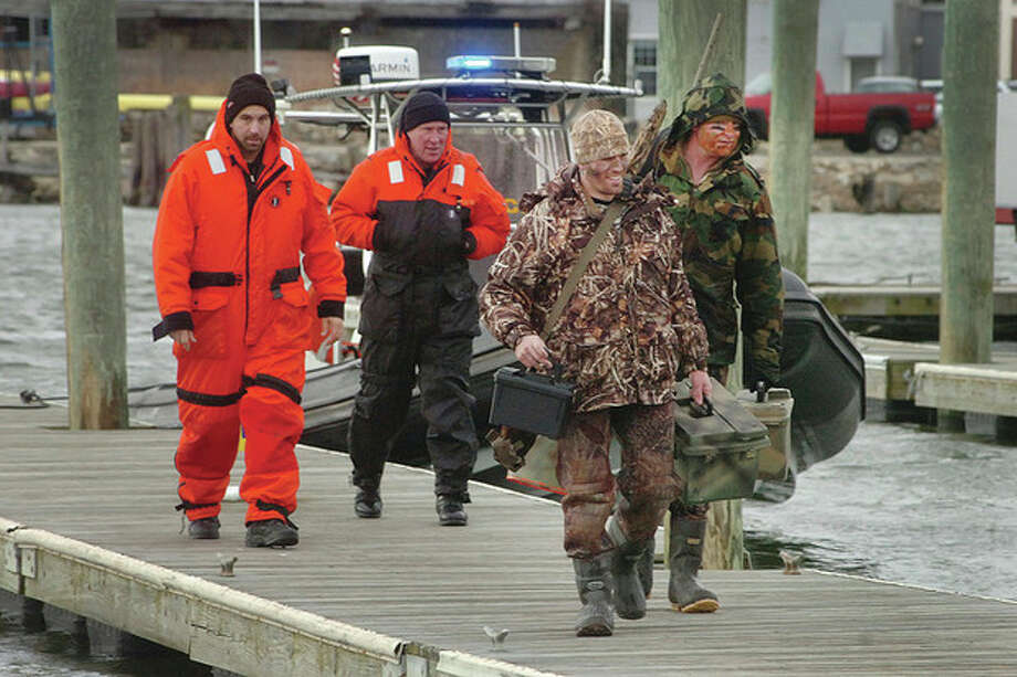 Hour Photo/ Alex von Kleydorff. Norwalk Marine Police bring back two duck hunters to safety after weather conditions worsened at Chimmon Island Friday afternoon. The hunters called for rescue after realizing high winds would make it too dangerous for them to cross the harbor back to Vets park. / ©2012 The Hour Newspapers