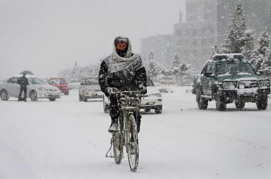 An Afghan man rides his bicycle during a snowstorm in Kabul, Afghanistan, Sunday, Jan. 22, 2012. (AP Photo/Musadeq Sadeq) / AP