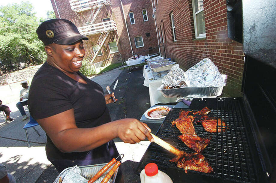 Photo/Alex von Kleydorff. Robin Peterson puts a little more barbeque sauce on the ribs and chicken during an appreciation picinic at Roodner Court on Friday. / © 2010 The Hour Newspapers/Alex von Kleydorff