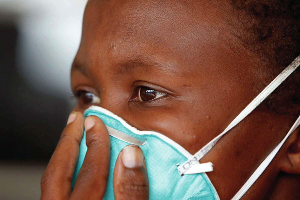 AP file photo / Schalk van Zuydam A woman suffering from tuberculosis covers her face at a clinic in the township of Khayelitsha, South Africa, in this file photo dated March 24, 2011.