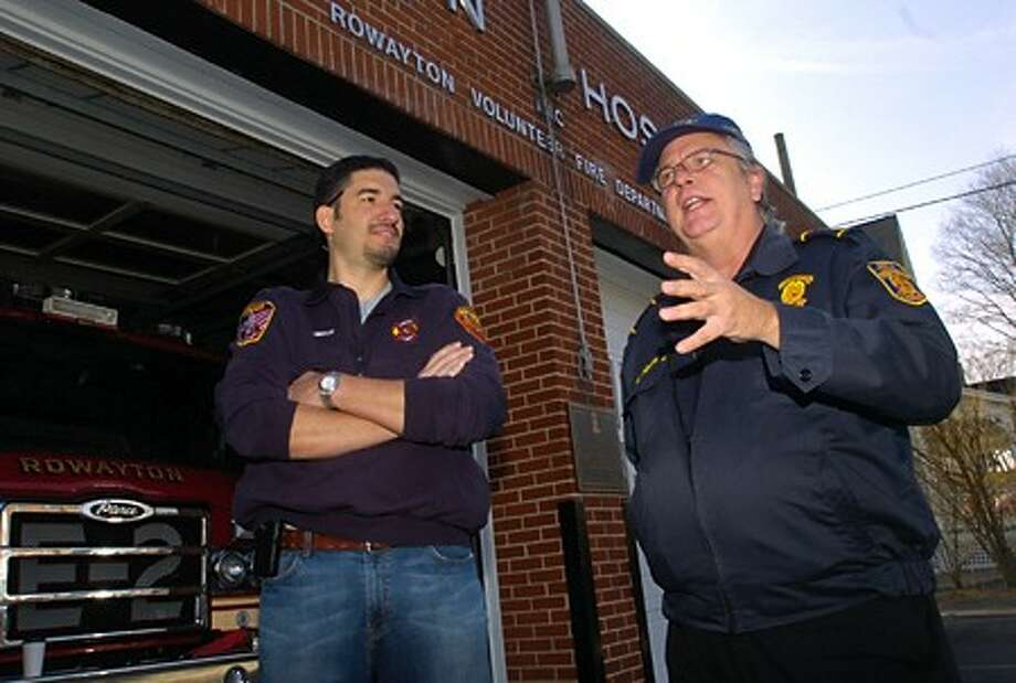 Rowayton volunteer firfighter Mark Pinzon greets Panamanian Fire Captain Luis Endara before the Rowayton Volunteer Fire Dpartment donated their 1982 ladder truck to Panama Friday morning. Hour photo / Erik Trautmann