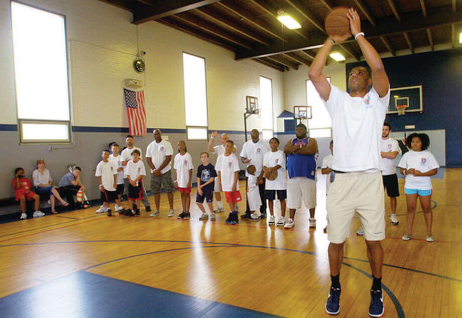 Former NY Knicks star and current Knicks executive Allan Houston works with children in the Father Child Mentor Program, also known as the F.I.S.L.L. (Faith, Integrity, Sacrifice, Leadership, Legacy) at the Norwalk Y Saturday. The Father Child Mentor Program is a seven-week series of two-hour sessions designed to provide fun and relationship-building opportunities for fathers or father-figures and their middle-school age boys and girls. / (C)2011, The Hour Newspapers, all rights reserved