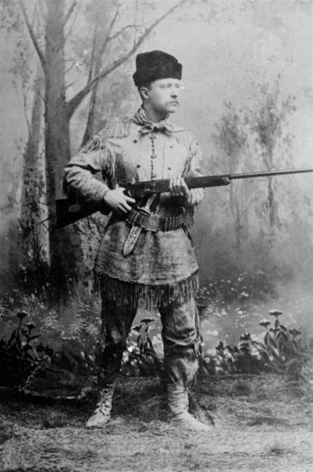 """FILE - In this undated file photo provided by Harvard University Press, President Theodore Roosevelt, posing as an """"outdoorsman,"""" points his rifle during a studio photo session. The White House has released a photo of President Barack Obama firing a gun, two days before he is set to travel to Minnesota to discuss gun control. It shows Obama shooting at clay targets on the range at Camp David, the presidential retreat in Maryland, where he says he engages in the sport """"all the time."""" The image was released at a time when Obama is pushing a package of gun-control measures in response to the Newtown, Conn., school shooting. But the image of a U.S. president holding a gun is certainly nothing new. (AP Photo/Harvard University Press, File)"""