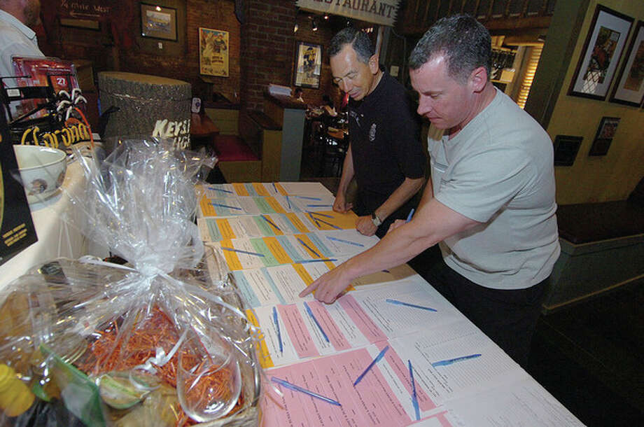 Hour Photo/Alex von Kleydorff. Dan Licitra writes a bid on Yankees Tickets as Norwalk's Community Policing officer Cesar Ramirez helps him with the Silent Auction items at Ash Creek Tip A Cop to benefit Special Olympics. / 2011 The Hour Newspapers