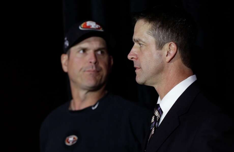 Brothers Jim Harbaugh, left, head coach for the San Francisco 49ers, and John Harbaugh, head coach for the Baltimore Ravens, arrive at a news conference for the upcoming Super Bowl XLVII in New Orleans, Friday, Feb. 1, 2013. (AP Photo/Gerald Herbert) / AP