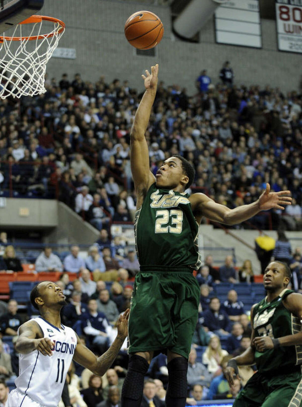 South Florida's Javontae Hawkins, right, shoots over Connecticut's Ryan Boatright during the first half of an NCAA college basketball game in Storrs, Conn., Sunday, Feb. 3, 2013. (AP Photo/Fred Beckham)
