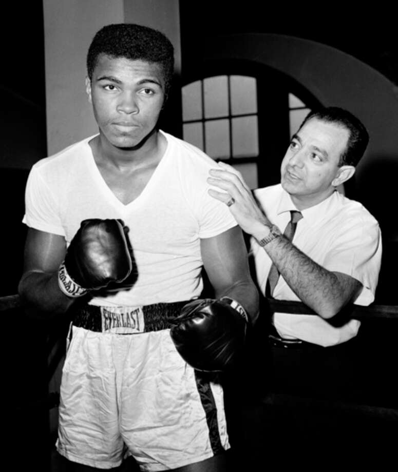 FILE - In this Feb. 8, 1962, file photo, a young Muhammad Ali, left, stands with his trainer Angelo Dundee at City Parks Gym in New York. Dundee, the trainer who helped groom Ali and Sugar Ray Leonard into world champions and became one of boxing's most recognizable figures, died Wednesday, Feb. 1, 2012. He was 90. (AP Photo/Dan Grossi, File) / AP1962