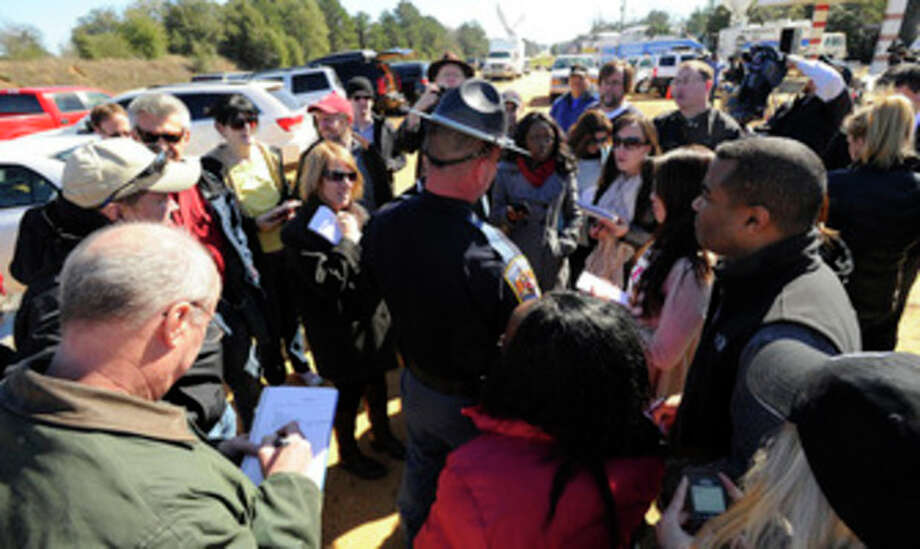 Alabama state trooper Kevin Cook, center right, is surrounded by members of the media following a news conference, Saturday, Feb. 2, 2013, in Midland City, Ala. Authorities said they still have an open line of communication with an Alabama man accused of abducting a 5-year-old child and holding him hostage in a bunker since Tuesday, Jan. 29. Sheriff Wally Olson said Saturday that Jimmy Lee Dykes has told them that he has blankets and an electric heater in the bunker. (AP Photo/al.com, Joe Songer) MAGS OUT. / al.com