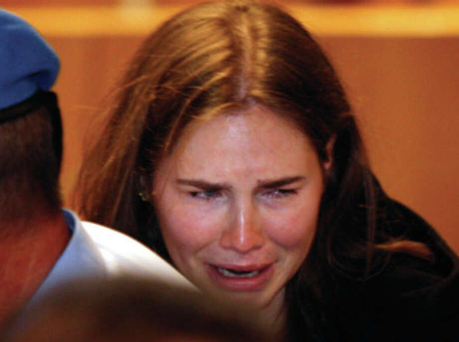 Amanda Knox breaks in tears after hearing the verdict that overturns her conviction and acquits her of murdering her British roommate Meredith Kercher, at the Perugia court, central Italy, Monday, Oct. 3, 2011. Italian appeals court threw out Amanda Knox's murder conviction Monday and ordered the young American freed after nearly four years in prison for the death of her British roommate Knox collapsed in tears after the verdict overturning her 2009 conviction was read out. Her co-defendant, Italian Raffaele Sollecito, also was cleared of killing 21-year-old Meredith Kercher in 2007. (AP Photo/Pier Paolo Cito) / AP