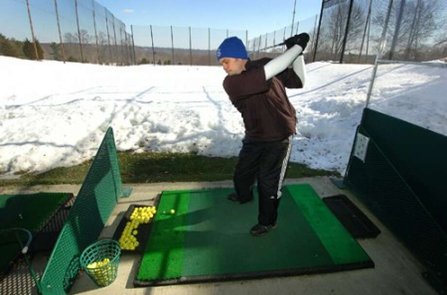 Photo/Alex von Kleydorff. Dan Buoncontri takes a swing at the Sterling Farms Golf Course Driving Range. There is always time to work on your game he says, using yellow colored balls in the snow helps the range staff find and collect them by hand one by one.