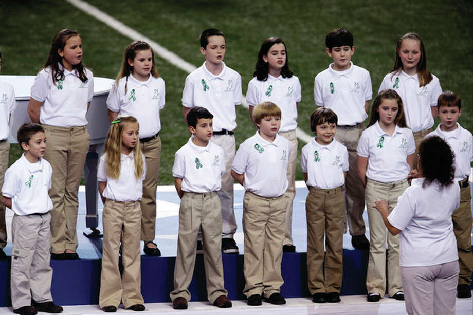 "Students from Sandy Hook Elementary School sing ""America the Beautiful"" before the NFL Super Bowl XLVII football game between the San Francisco 49ers and the Baltimore Ravens, Sunday, Feb. 3, 2013, in New Orleans. (AP Photo/Charlie Riedel) / AP"