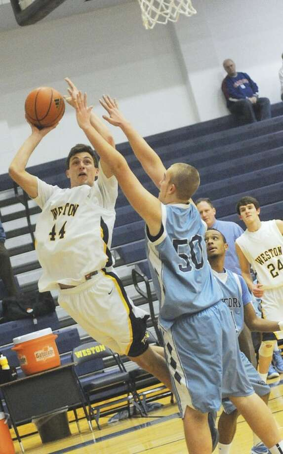 Hour photo/Matthew Vinci Weston's Lyle Mitchell goes up for a shot as J.T. Van Kamerik of Oxford defends during Tuesday night's contest in Weston. The Trojans won, 75-54.