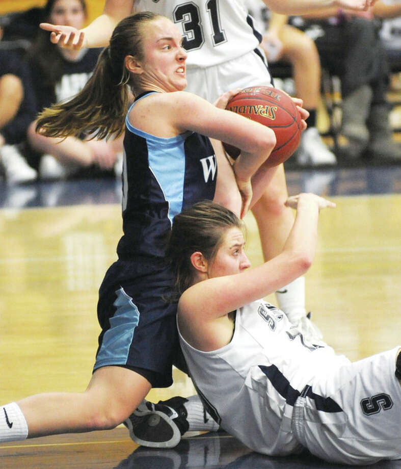 Wilton's Maddy Fulton, top, ties up Jess Coelho of Staples during the second half of Tuesday's game in Westport. The Wreckers rallied in the final minutes for a 53-48 victory. @Cutline Byline:Hour photo/ John Nash