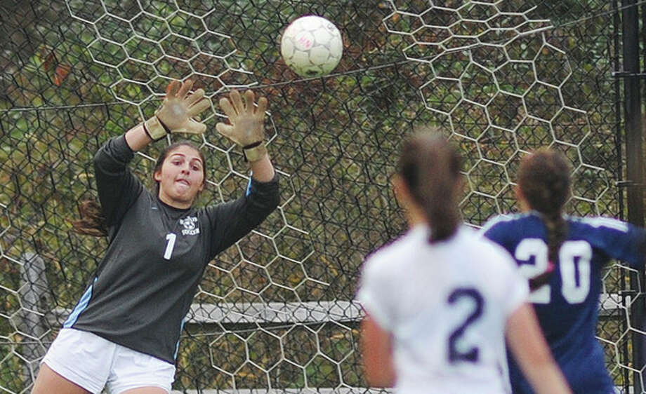 Hour photo/John Nash Wilton goalkeeper Kasey O'Brien, left, keeps her eyes on a shot by Abbey Lake (20) of Staples as Wilton's J.J. Munro (2) looks on. The two teams battled to a 1-1 tie.