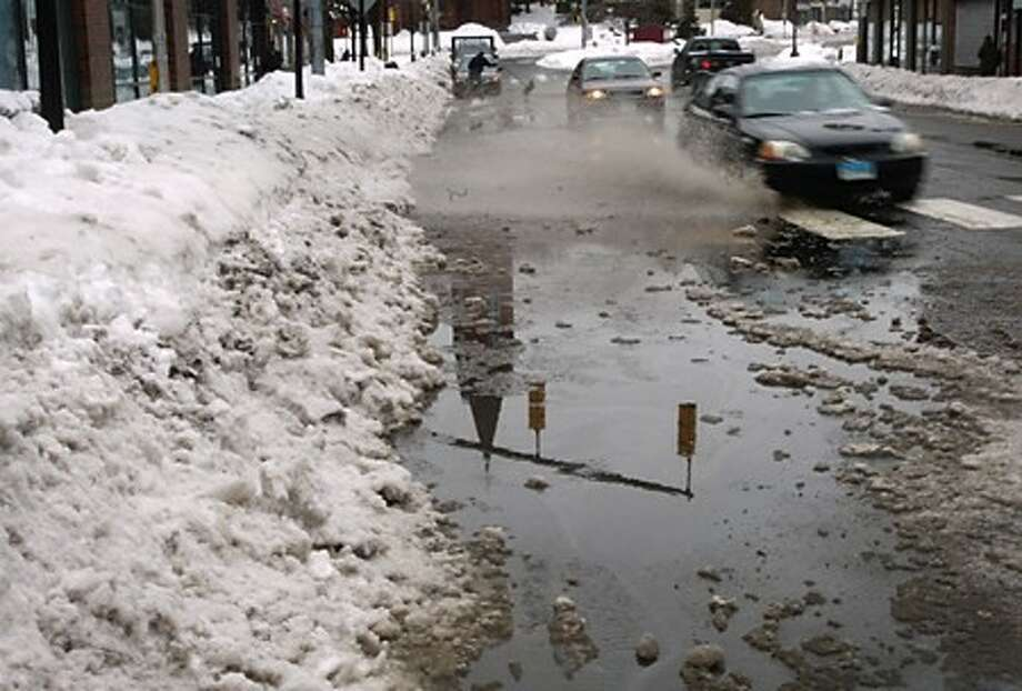Storm drains blocked by snow and ice cause flooding on North Main St in Norwalk Wednesday. Hour photo / Erik Trautmann