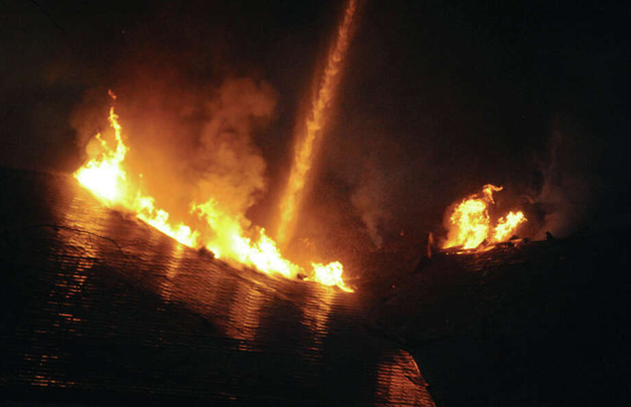 Hour Photo/John Nash - The roof of the Saugatuck Congregational Church burns during a fire in Westport on Sunday night.