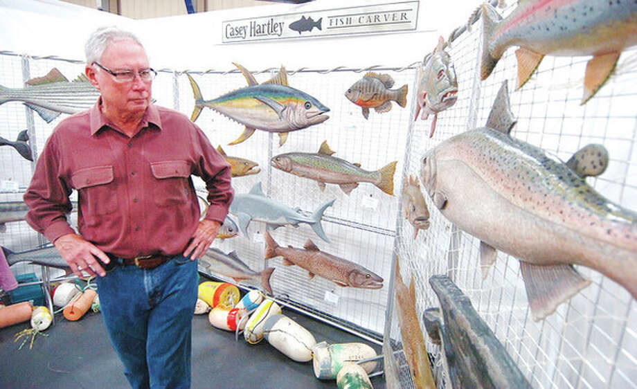 Photo/Alex von Kleydorff. Bob Gilman looks over the selection of hand carved fish by artist Casey Hartlet at the Craftmanship show in Wilton.