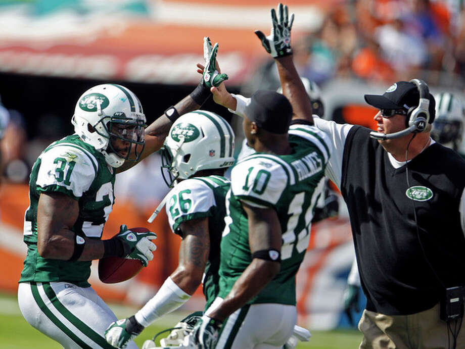 New York Jets cornerback Antonio Cromartie (31) is congratulated by defensive back Ellis Lankster (26), wide receiver Santonio Holmes (10) and head coach Rex Ryan after an interception during the first half of an NFL football game against the Miami Dolphins, Sunday, Jan. 1, 2012, in Miami. (AP Photo/Lynne Sladky) / AP