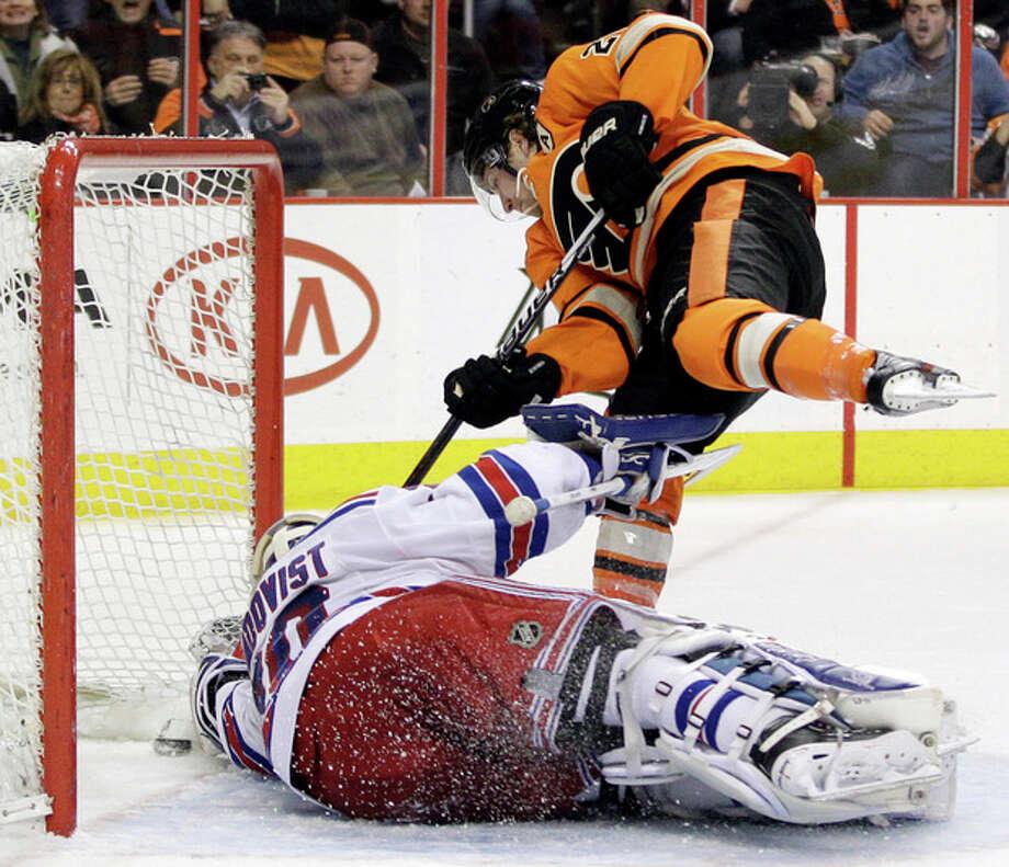 Philadelphia Flyers' Claude Giroux, top, scores a goal past New York Rangers' Henrik Lundqvist, of Sweden, in the second period of an NHL hockey game, Saturday, Feb. 11, 2012, in Philadelphia. (AP Photo/Matt Slocum) / AP