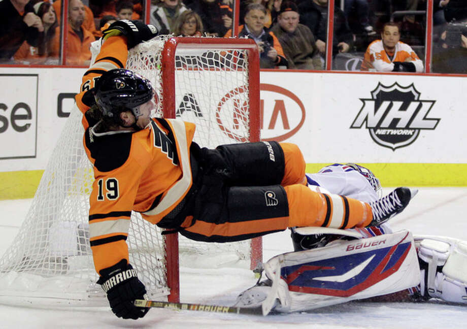 Philadelphia Flyers' Scott Hartnell, left, collides with New York Rangers' Henrik Lundqvist, of Sweden, in the second period of an NHL hockey game, Saturday, Feb. 11, 2012, in Philadelphia. Hartnell was given a penalty for goaltender interference on the play. (AP Photo/Matt Slocum) / AP