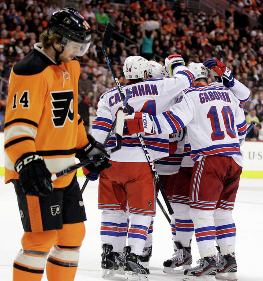 New York Rangers' Marian Gaborik (10), of Slovakia, and Ryan Callahan (24) celebrate with teammates after Gaborik's goal as Philadelphia Flyers' Sean Couturier (14) skates by in the first period of an NHL hockey game, Saturday, Feb. 11, 2012, in Philadelphia. (AP Photo/Matt Slocum) / AP