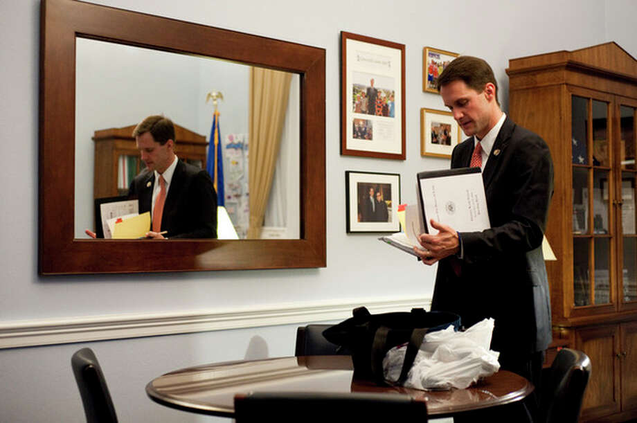 """Nov. 19, 2009-Rep. Himes packs up for the flight home, just after scheduler Caitlin Donohue informs him the plane has been delayed for the second time this evening.""""The hardest part of my job is being away from my family,"""" Himes said. """"I have a wife and two girls at home and I don't want to be an absent dad."""" Rep. Himes lives with his wife and two daughters, Emma and Linley in Cos Cob, Conn. / ©caroline treadway 2009"""