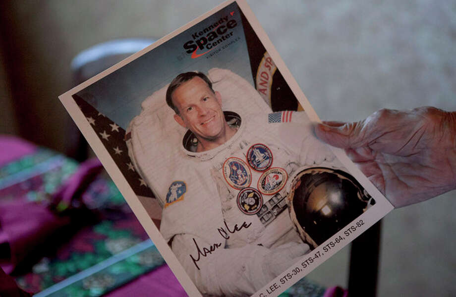 In this Dec. 28, 2011 photo, 100-year-old Minka Disbrow shows an autographed photo of her grandson Mark Lee, a space shuttle astronaut, during an interview with the Associated Press in San Clemente, Calif. Disbrow, who was raped at age 16, has lived to be 100 - long enough to meet the daughter she gave up at birth 77 years earlier and learn about the six grandchildren she didn't know she had, including Mark Lee. (AP Photo/Jae C. Hong) / AP