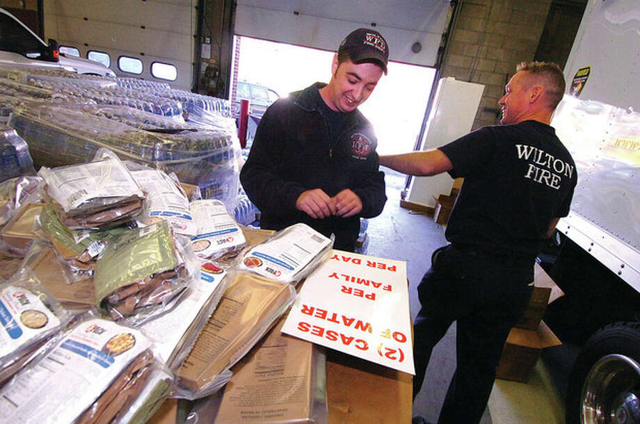 File Photo/ Alex von Kleydorff. Wilton Firefighters Bill Wilson and Jim Blanchfield organize some of the bottled drinking water and a pallet of emergency meals for distribution to residents without power after a rare pre-Halloween snowstorm last month. / 2011 The Hour Newspapers