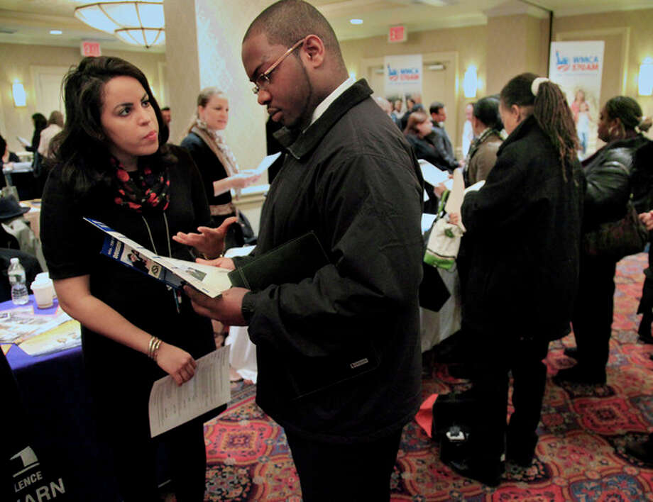 In this Jan. 25, 2012 photo, Daniela Silvero,left, an admissions officer at ASA College, discuss job opportunities with Patrick Rosarie, who is seeking a job in IT, during JobEXPO's job fair, in New York. The unemployment rate fell for the fifth straight month after a surge of January hiring, a promising shift in the nation's outlook for job growth. (AP Photo/Bebeto Matthews) / AP