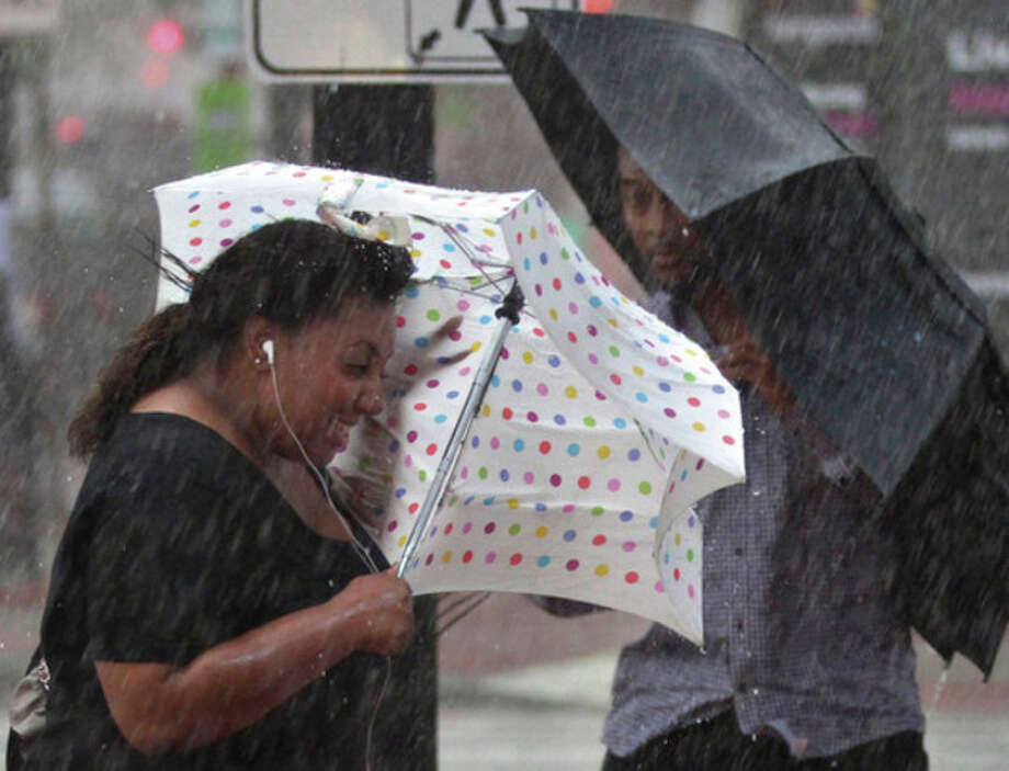 Pedestrians with umbrellas struggle against a blast of wind and rain from Hurricane Irene in downtown Washington late Saturday afternoon, Aug. 27, 2011. (AP Photo/J. Scott Applewhite) / AP