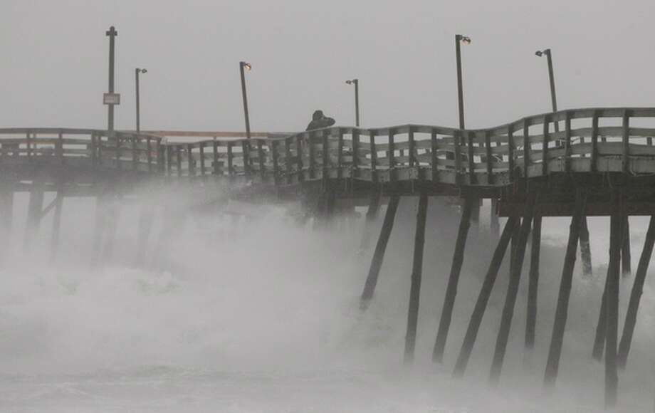 AP Photo/Charles Dharapak Denis Hromin, a concerned fisherman, checks on Avalon Fishing Pier as it lost some pilings after being battered by wind and waves on the Outer Banks in Kill Devil Hills, N.C., Saturday as Hurricane Irene reaches the North Carolina coast. / AP