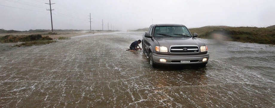Ron Briethaup, 48, of Buxton, N.C. works to free his fiancee's truck after it got stuck on a flooded section of Hwy 12 just north of Hatteras Village, N.C. Conditions had been improving so she had gone out to run an errand, but hurricane force winds picked up again with no warning and she became stranded. Briethaup came to the rescue and dug the wheels out by hand as the wind howled at 77 mph. He said, / 2011 The News & Observer